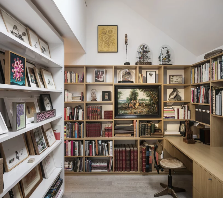 The study features endless bookshelves and a built-in desk plus some artworks