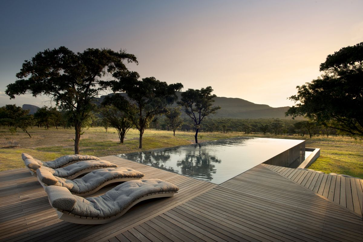 The swimming pool is perfectly level with the deck and reflects the beautiful landscape around it