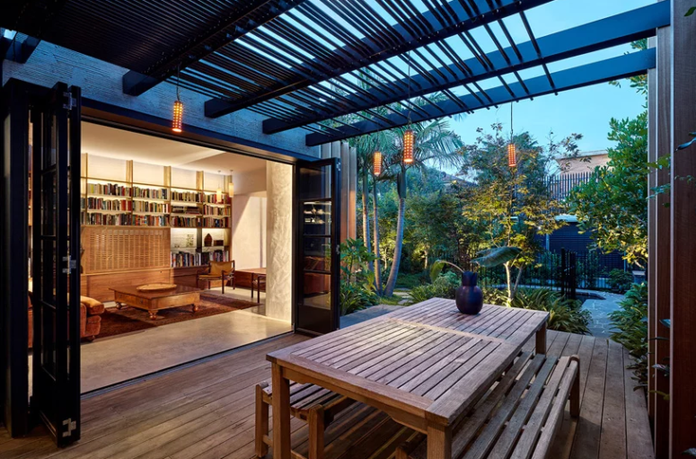 The terrace is done with much wood and a simple dining set, the folding doors open indoor spaces to it