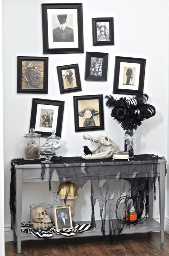 a Halloween console with black tulle, skulls of animals and humans, a spooky gallery wall and a black feather arrangement