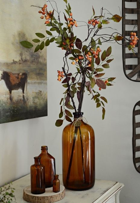 fresh branches with greenery and berries put into amber bottles will make nice fall decor