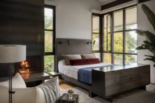 09 The bedroom features dark wood and metal, a hearth and amazing views
