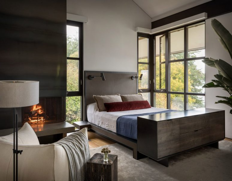 The bedroom features dark wood and metal, a hearth and amazing views
