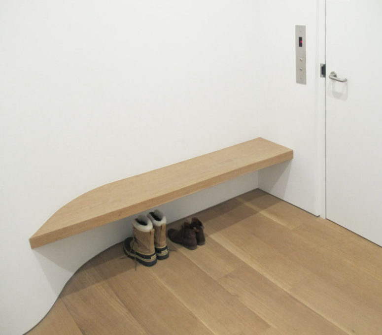 The entryway features just a buiilt-in bench and curves to make the space more interesting
