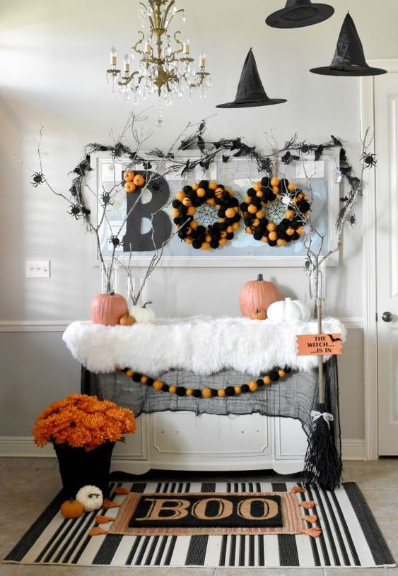 a Halloween entryway console with a printed rug, a bold floral arrangement, pompom wreaths, branches with spiders and witches' hats