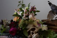 09 a moody Halloween centerpiece of a skull plus some blush and purple blooms and greenery and herbs