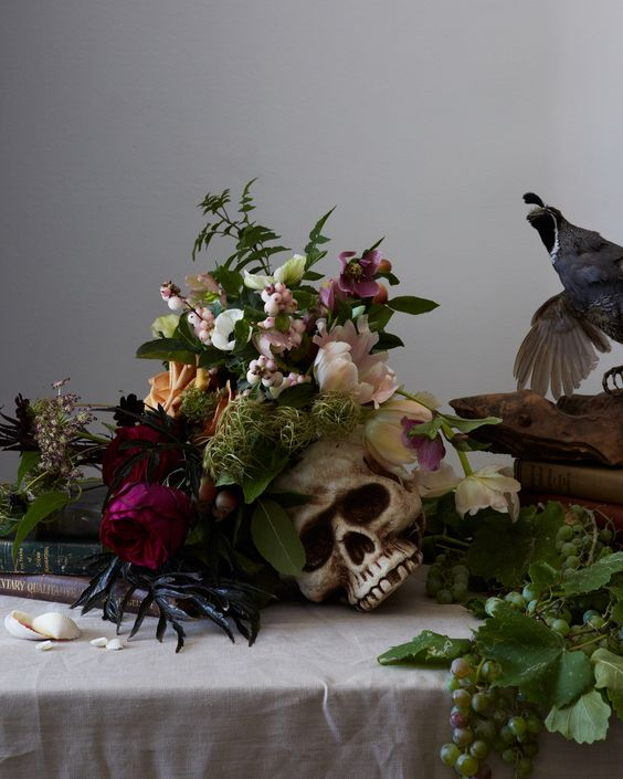 a moody Halloween centerpiece of a skull plus some blush and purple blooms and greenery and herbs