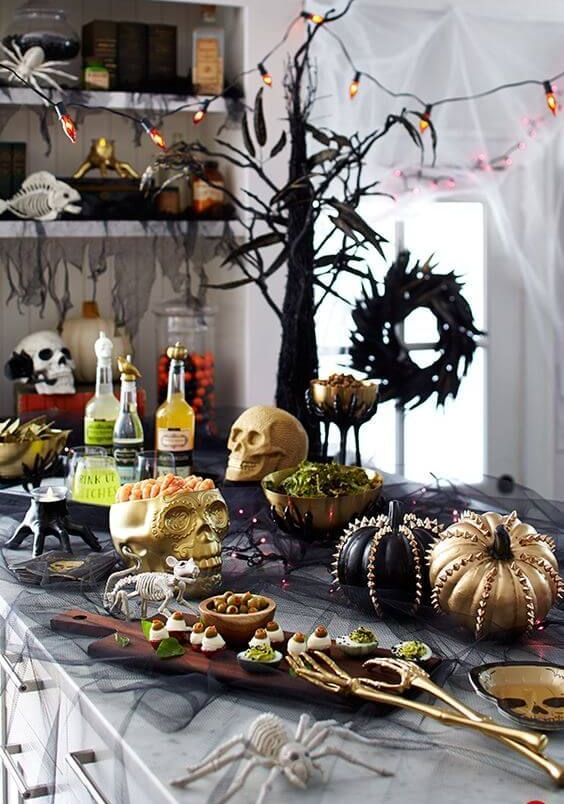 a stylish Halloween food station with skulls, lights, studded pumpkins, spiders and skeletons plus tasty food