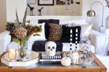 10 Halloween coffee table decor with a skull, skulls in a cloche, pumpkins, dried blooms and feathers plus candles