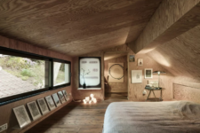 10 The master bedroom is designed like a cabin and is all clad with light-colored plywood, there some lights, art and a work space