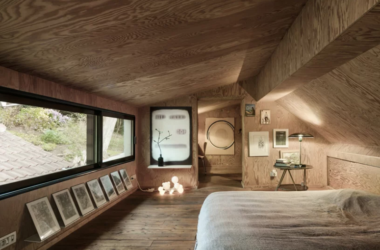 The master bedroom is designed like a cabin and is all clad with light-colored plywood, there some lights, art and a work space