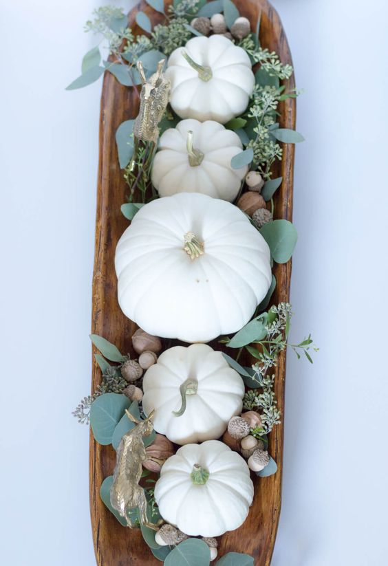 a fall centerpiece of a wooden bowl, acorns, greenery and white pumpkins   everything natural here