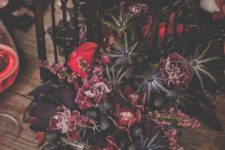 10 a gorgeous and sultry Halloween centerpiece of a black lantern, fuchsia and red blooms, thistles and grapes