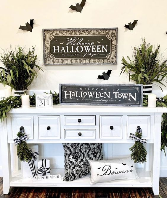 a simple and fresh Halloween entryway console with black and white pillows, greenery arrangements, signs and candles is chic