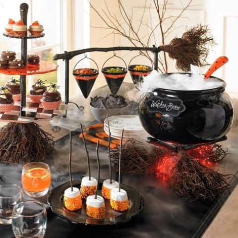 a stylish Halloween food and drink station with a cauldron with drinks, a broom with witch hats for food serving, drinks and sweets that match