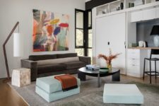 Mint poufs and a colorful artwork fill the monochromatic space with life