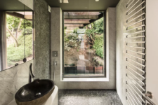 11 The bathroom opens towards nature and is decorated with pebbles and marble tiles