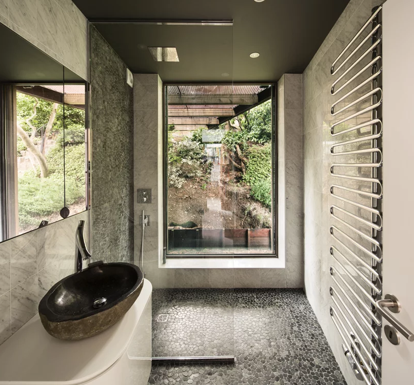 The bathroom opens towards nature and is decorated with pebbles and marble tiles