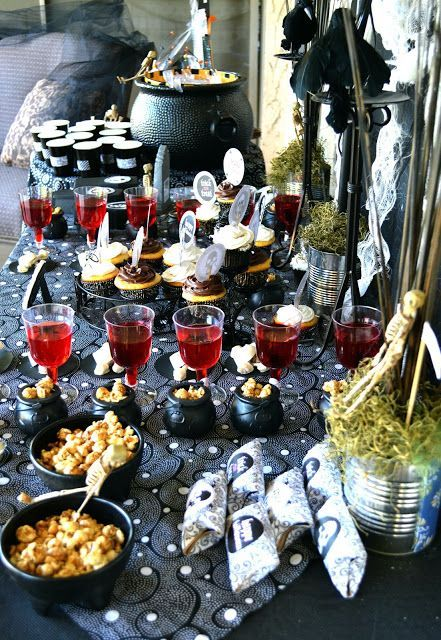 a stylish Halloween buffet with little black cauldrons for food, red bloody drinks, a large cauldron with bottles and skeletons