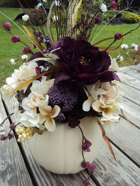 a white pumpkin centerpiece with neutral and deep purple flowers, berries and branches for Halloween