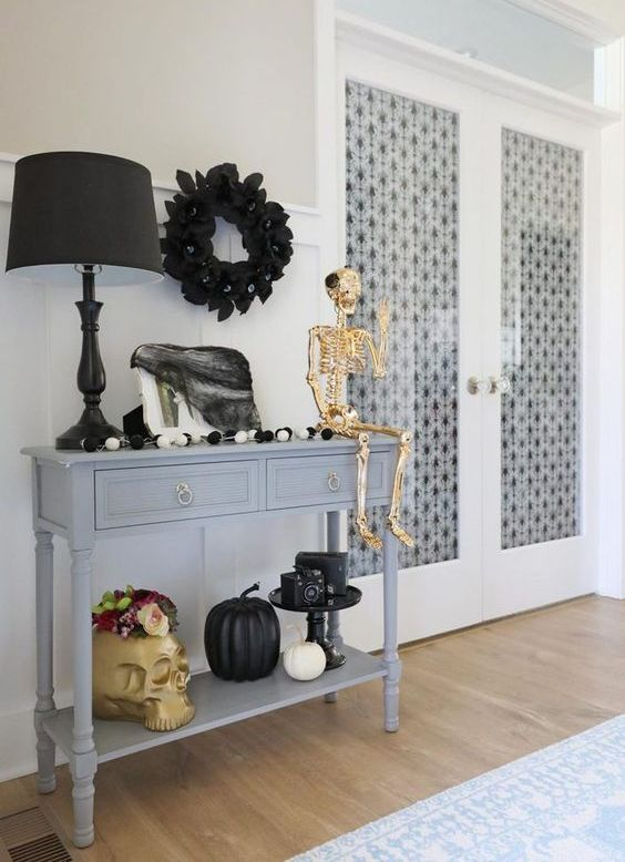 an entryway console decorated with a giant skull, a gold skeleton, black and white pumpkins, a black wreath and tulle