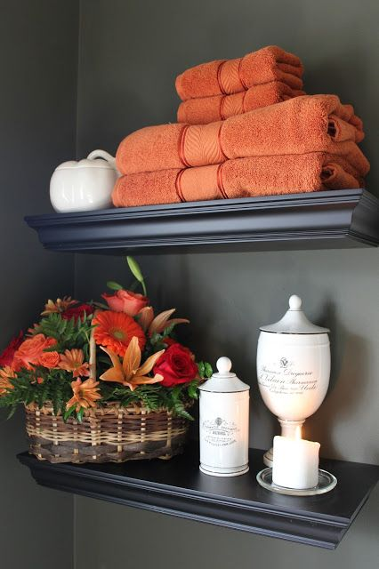 orange towels and a bright fall bloom arrangement in a basket will make your bathroom feel like fall