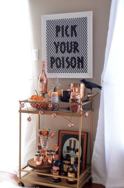 a chic Halloween bar cart with a sign, blackbirds, a garland and lots of copper touches and details