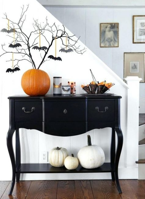 an elegant black console table with white pumpkins, an orange pumpkin as a vase, black branches with bats and bat candleholders