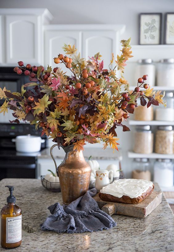 a beautiful fall arrangement of fall leaves and berries in a vintage metal jug is amazing for home decor