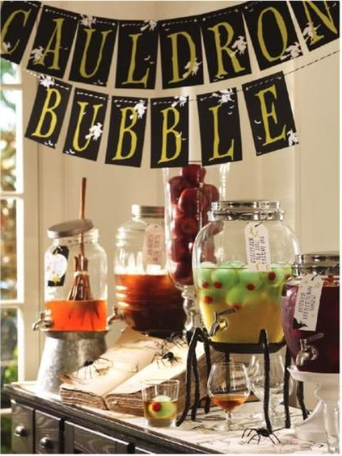 a cool drink station decorated with a bunting over the table, a broom stirrer, eyeballs and a spellbook
