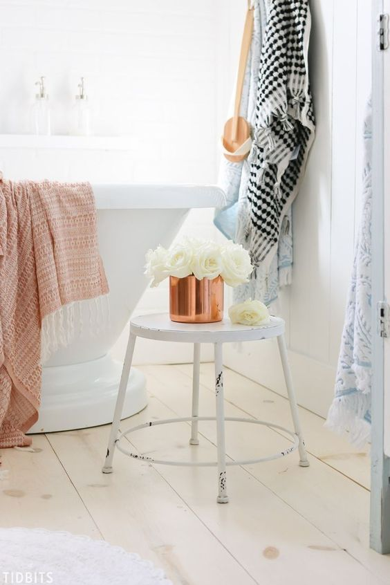 a copper pot with white roses and a copper towel are easy details to bring a fall feel to the space