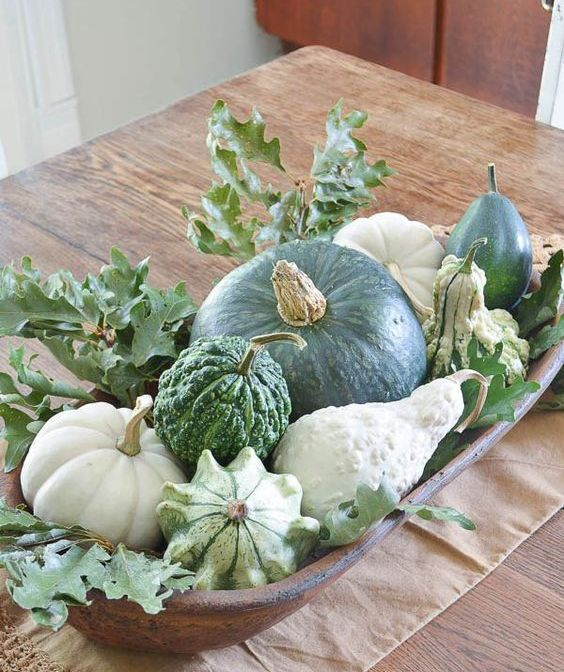 a dough bowl with pumpkins, gourds and freen leaves will make up an amazing fall centerpiece