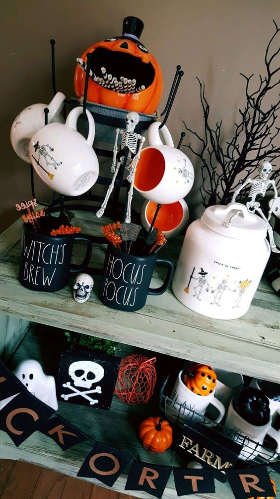 a drink station with cool Halloween mugs, a pumpkin with straws, a skeleton and some branches and Halloween pumpkins