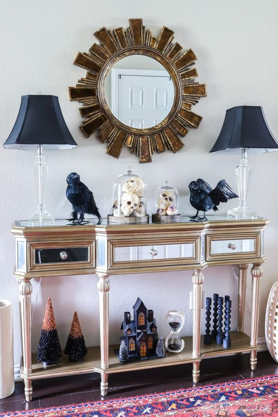 a refined entryway console with black lamps, blackbirds, black candleholders, a black house and Halloween trees