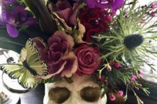 14 a skull centerpiece with a lush floral arrangement in purple, pink, green, with thistles and butterflies plus large leaves