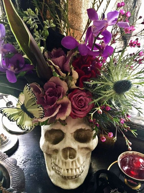 a skull centerpiece with a lush floral arrangement in purple, pink, green, with thistles and butterflies plus large leaves