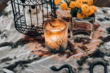 14 stylish Halloween coffee table decor with a splatted tablecloth, a cage with a plush, a candleholder and bold blooms in a vase