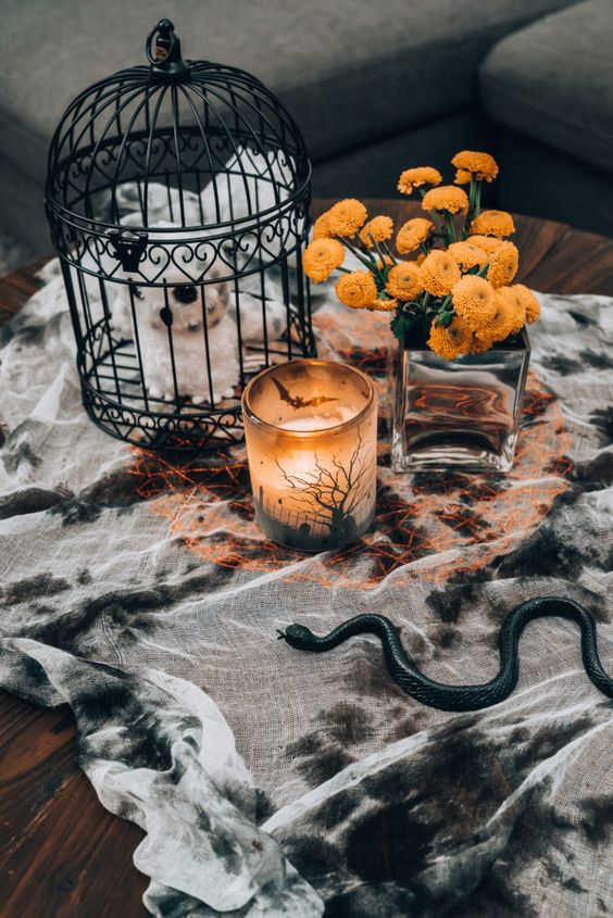 stylish Halloween coffee table decor with a splatted tablecloth, a cage with a plush, a candleholder and bold blooms in a vase
