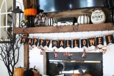 15 a bold Halloween mantel with a bunting, fake pumpkins including carved ones, decorated and lettered ones, lanterns and a spooky tree