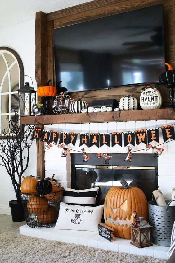 a bold Halloween mantel with a bunting, fake pumpkins including carved ones, decorated and lettered ones, lanterns and a spooky tree