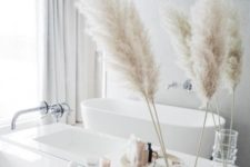15 a dried grass arrangement in a clear vase is a cool fall accent for a contemporary or minimalist bathroom