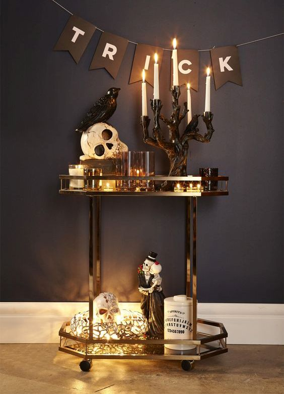a glam Halloween bar cart with candles, lights, skulls, figurines and a bunting   just add some drinks and voila
