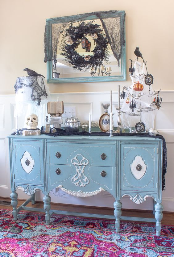 a refined Halloween console with an antler Halloween tree with black and orange ornaments, skulls, blackbirds and a dramatic black wreath