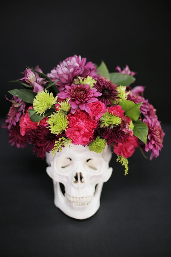 a skull with a bold flroal arrangement in pink, red and green plus some leaves is a timeless idea