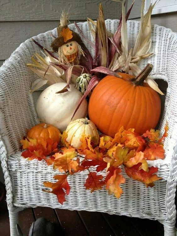 a white chair decorated with fall leaves, pumpkins, corn husks and some greenery will spruce up your home or porch