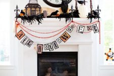 16 a bold Halloween mantel with a colorful bunting, blackbirds, feathers, a cage, candles and pumpkins