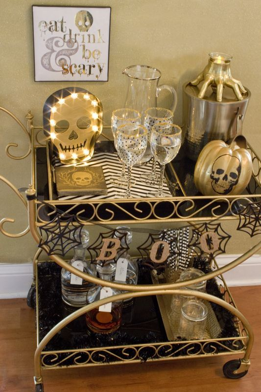 a gorgeous black and gold Halloween bar cart with skeletons, striped mats, a garland with spiderwebs and a hand candleholder