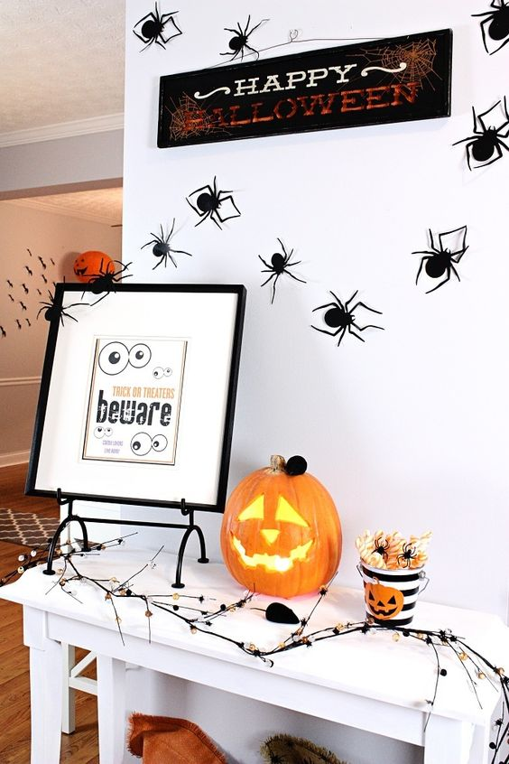 a Halloween entryway console with a Jack-o-lantern, a sign, some spiders and art and a creepy branch