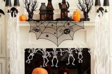 17 a bright Halloween mantel with carved pumpkins, skeletons, a piderweb, haunted houses and a banner over it