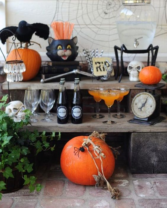 a Halloween drink bar with a pumpkin, skulls, blackbirds, spiderweb, greenery and skeleton hands